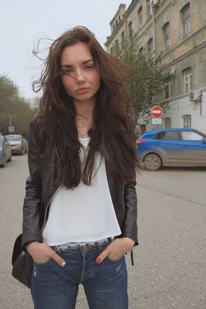 Melancholy mood. Sexy sad woman posing outside in jeans leaser jacket with her hands inside pockets