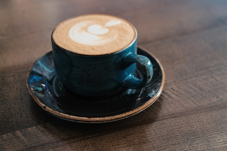 Side view of Coffee cup with perfect latte art on foam on tabletop with copy-space.