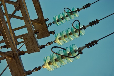 High voltage lines and a glass insulators. Closeup of high voltage lines with insulators and a minor part of a power pylon against a blue sky on a sunny day crossprocessed colors and copyspace Imagens