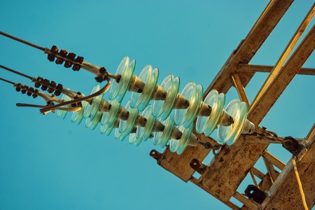 Glass electrical insulators on power-tower from below view Archivio Fotografico