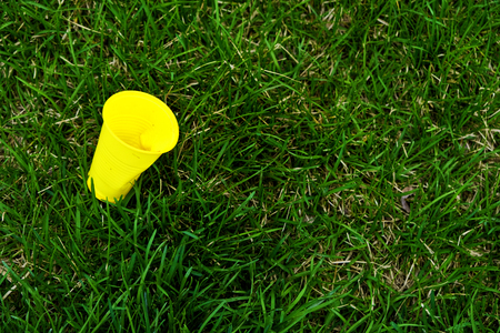 Yellow plastic cup lying over fresh green grass. Environmental issues - plastic contaminates our common homeplanet Earth