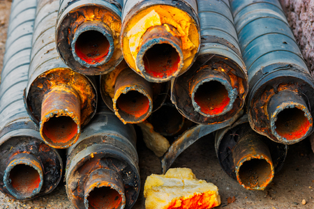 Many corroded rusty pipes with footprint of welding on side