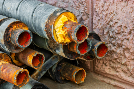 Water Pipeline repair. Rusty steel pipe with insulation on the construction site in a plastic foam tube wrapper lying on the yard in a bunch horizontally. Rusty old pipeline stacked up near the wall