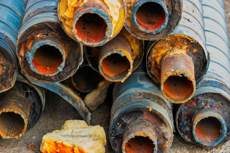 Water Pipeline repair. Large rusty steel pipe with insulation on the construction site in a plastic tube wrapper lying on the yard in a bunch horizontally. Rusty old pipeline stacked up