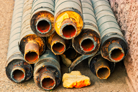 Bunch of old rusty pipes lying on the ground ready for utilization view from ends