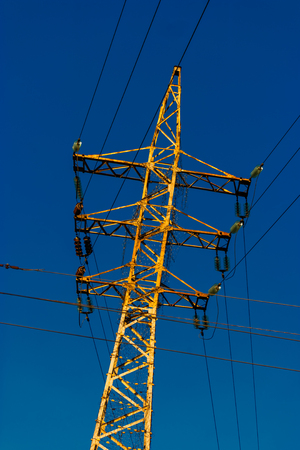 Rusty power-tower with many wires and glass insulators dutch angle shot image. Archivio Fotografico