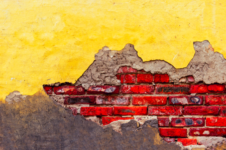 Distressed brick wall with cracks and broken yellow plaster half destroyed wall cover, a lot of copyspace.