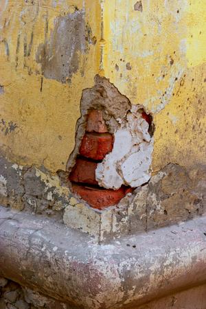 Corner of the old building made of red bricks hald destroyed plaster on it