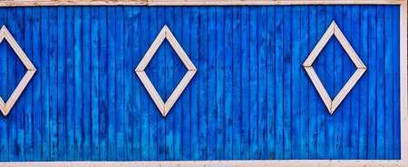 Rural wooden fence painted in blue color with some decorative element Imagens