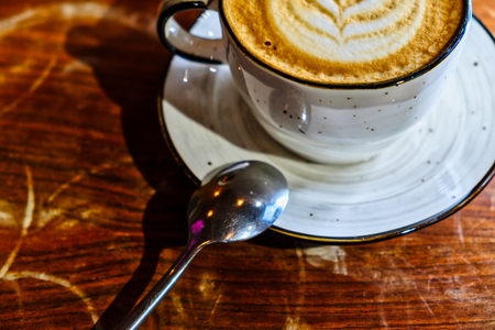 Coffee cup with cappuccino on the worn polished tabletop, detail above view image 写真素材