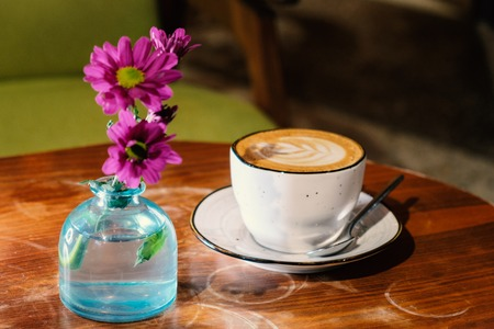 Coffee cup with cappuccino and pink flowers in glass bottle on the worn polished tabletop side view image