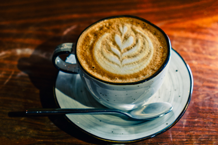 Coffee cup with cappuccino on the worn polished tabletop above view image