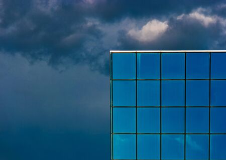 Skyscraper Tiled Windows And Dark Cloudy Sky Stock Photo