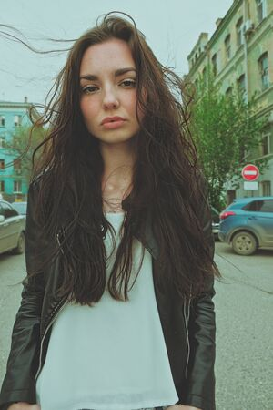 Peaceful looking girl posing with messy windy hair ouside, wide angle smartphone lens imitation vertical image Banque d'images
