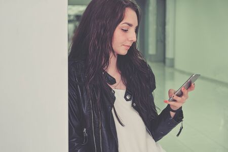 A beautiful girl uses a smartphone in an office building leaning against a wall shot with copyspace