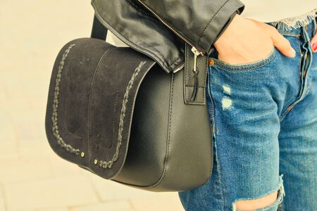 Young woman hold yoyr hand in pocket wih black handbag on her shoulder wearing riped jeans