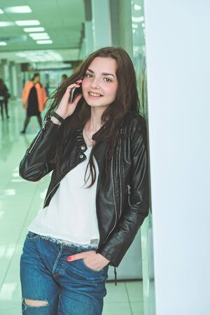 Portrait of beautiful brunette woman chatting via smartphone spending time in office interior, pretty hipster girl looking at camera using mobile phone for communication vertical image