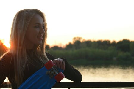 Blond hair woman posing with her scateboard smiling in front of sunset on waterfront with a lot of copyspace Stok Fotoğraf