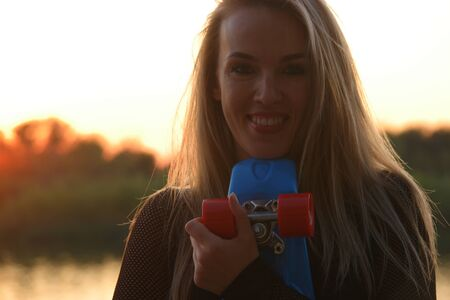Blond hair woman posing smiling with her chin touching scateboard in front of sunset on waterfront, front view Stok Fotoğraf
