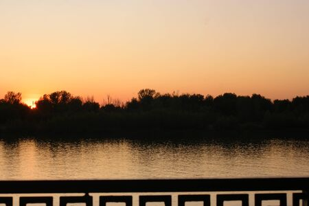 Sunset time on the river with fence of embankment sidewalk on foreground