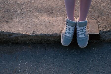 Female runner standing on the edge of concrete pavement in city center, closeup on shoes top view, a lot of copyspace. Imagens