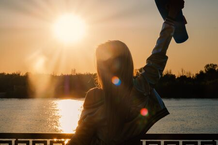 Woman posing with her hands holding skateboard raised up in the sunset sky, summer farewell concept. Sunflares all over the low conbtrast image