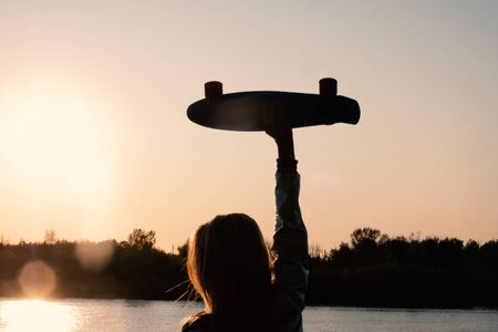 Silhouetted Woman posing with her hands holding skateboard raised up in the sunset sky, summer farewell concept. 版權商用圖片