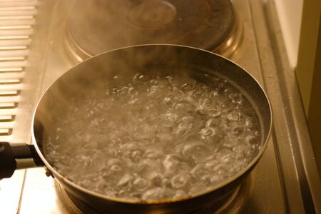 Water in the pot boiling close up with steam above 스톡 콘텐츠