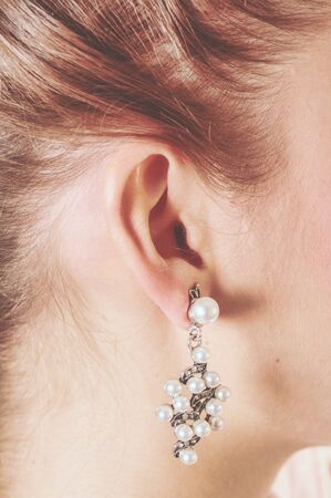 Picture of the tender ear of a girl carrying an earring with many pearls. Vintage colors are similar to those of an old photo.