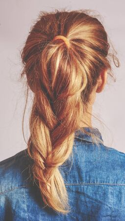 The back side view of a young unrecognizable woman with blond hair woven into a sloppy, stylish French-style braid.