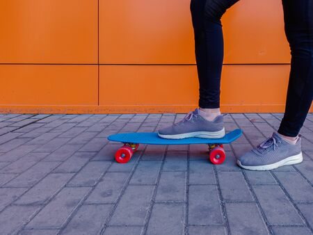 A picture of a girl who put her foot in sneakers on a skateboard against bright orange wall