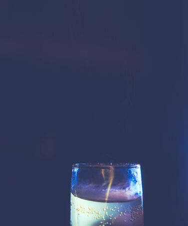 A small glass with liqueur with colorful reflections of light of different colors stands on a dark background. Lots of copypace. Minimal design stylized as a hipster-style film photo.