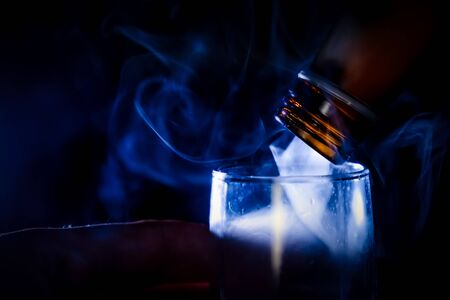 The man holding shot of dring in his hand and flow of steam or evil spirit flow out of and fill in the glass, shot on dark background. Kho ảnh