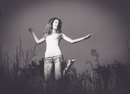 Black and white image of joyful girl dancing in the tall grass in the night