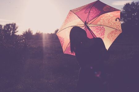 Unrecognizable silhouette of the lady with backlit umbrella full of sunshine glow
