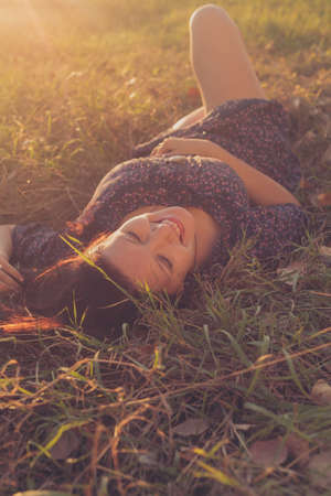 Happy girl in lying in tall grass in the fields, view from the top of the head side. Copyspace on foreground. Zdjęcie Seryjne