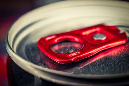 Macro photografy of lid of metal can of fizzy drink with bright red ring-opener