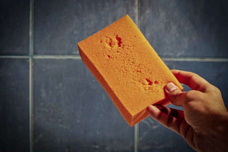 Orange sponge for washing in mans hand in bathroom, copyspace on the tiled wall