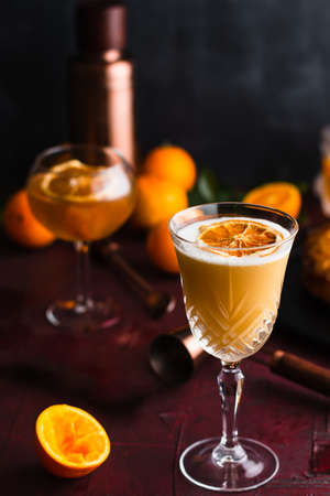 Goblet glass containing a whiskey sour garnished with a dried orange