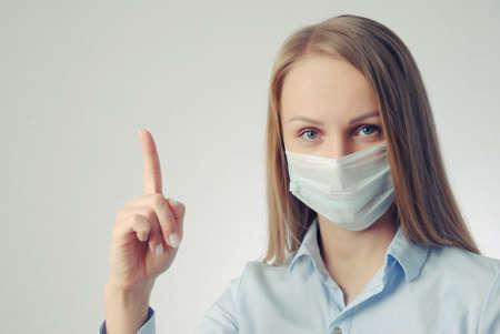 girl in medical mask points finger up Reklamní fotografie