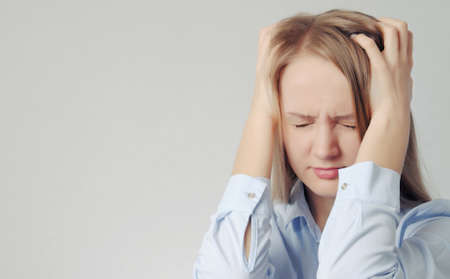 young blonde girl holds her head. Woman with headache