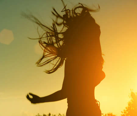 female silhouette with an emotional splash. musician or actor in courage against the backdrop of a beautiful sunset