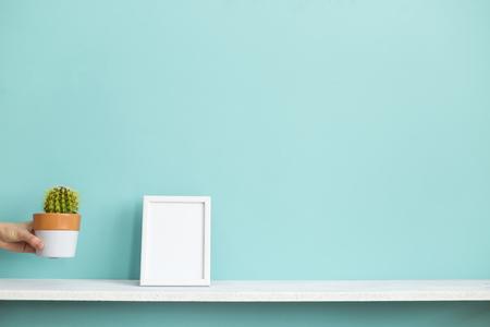 Decoración de habitación moderna con maqueta de marco de imagen. Estante blanco contra la pared de color turquesa pastel con la mano bajando la planta de cactus en maceta. Foto de archivo