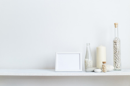 Modern room decoration with picture frame mockup. Shelf against white wall with decorative candle, glass and rocks.