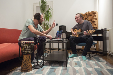 Two professional musician recording and playing instruments in digital studio at home. They are surrounded with instruments and midi controller. Music production concept.