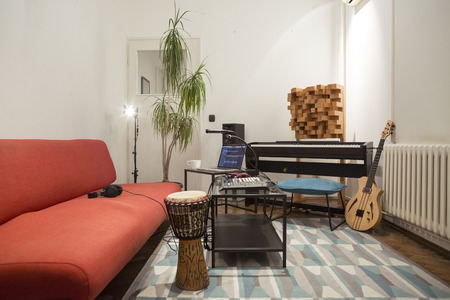 Professional digital studio at home for recording. He has instruments and midi controller. Music production concept.