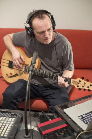 Professional musician recording electric guitar in digital studio at home. He is surrounded with instruments and midi controller. Music production concept. Banque d'images