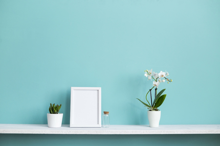 Modern room decoration with Picture frame mockup. White shelf against pastel turquoise wall with potted orchid and succulent plant.