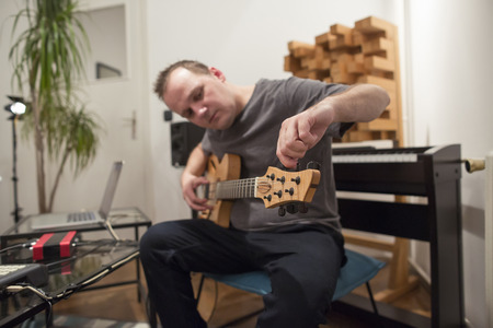 Professional musician tuning electric guitar in digital studio at home. He is surrounded with instruments and midi controller. Music production concept.