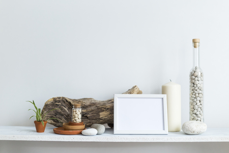 Modern room decoration with picture frame mockup. Shelf against white wall with decorative candle, glass, wood and rocks. Home plant in pot.